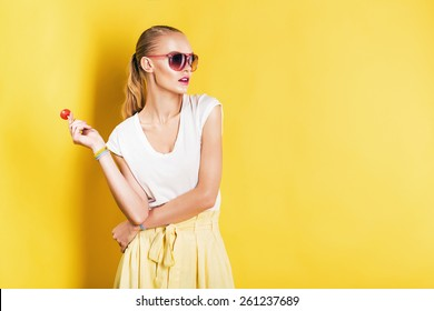 attractive woman in white top with lollipop in hand on yellow background