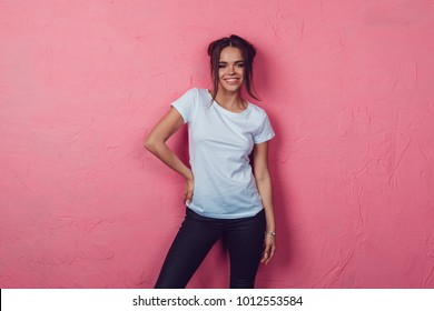 Attractive woman in a white t-shirt stands on a pink background. Mock-up.