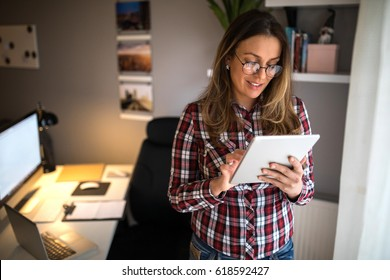 Attractive woman working on a tablet in a home office.