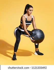 Attractive woman workout with med ball. Photo of sporty latin woman in fashionable sportswear on yellow background. Strength and motivation.