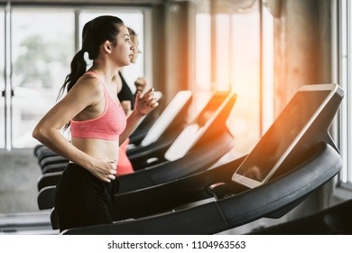 attractive woman workout on treadmill run track with music from earphone with happiness in gym