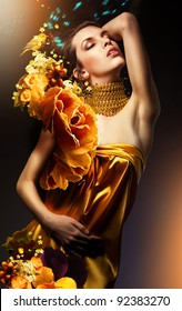 attractive woman in yellow dress with jewelry and flowers