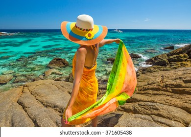 Attractive woman with yellow sarong and wide-brimmed hat looks the tropical turquoise sea from windy cliff of Racha Noi island, Rawai province, Andaman Sea, Thailand