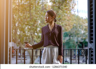 Attractive women elegantly dressed drinking red wine on the balcony of apartment. Beautiful businesswomen enjoying a red wine outdoors. - Image