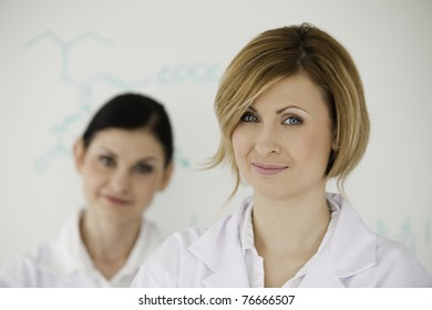 Attractive women in front of a white board in a lab