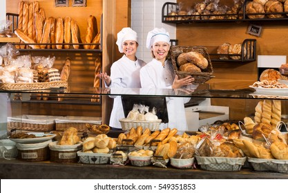Attractive women selling fresh pastry and loaves in bread section and smiling