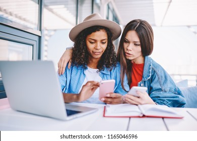 Attractive women sharing information on smartphone devices sitting at table with laptop computer using good wireless connection,multicultural hipster girls messaging with followers via app on cellular