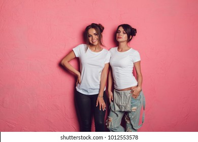 Attractive women in a white t-shirts stands on a pink background. Mock-up.