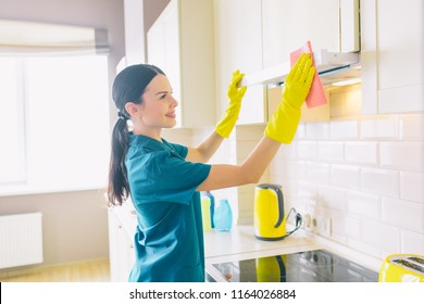 Attractive worker stands at cupboard and clean it. She has blue uniform and yellow gloves. Girl smiles.
