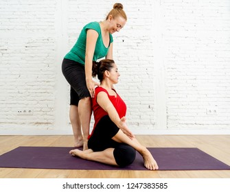 Attractive Yoga coach instructor teaching young woman Half lord of the fishes pose in studio home as Private yoga lessons Wellness Fitness and emotional physical and mental Well being concept.
