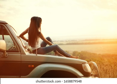 Attractive yong woman is sitting on the car's hood and looking at sunset. Rural evening background.