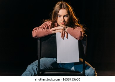 attractive young actress with scenario sitting on chair on stage in theatre