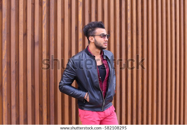 Attractive Young Adult Arabian Man Poses Into Camera, Corrects Hairstyle and Smiles, Waits For Meeting and Advertises Male Sunglasses, Looks Around Wearing Glasses and Stands on Background of Wooden