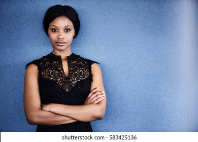 Attractive young adult black woman looking into camera with her arms crossed and a serious facial expression with a blue textured background behind her.