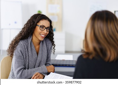 Attractive young African American businesswoman wearing glasses in an interview with a female manageress listening attentively to the questions