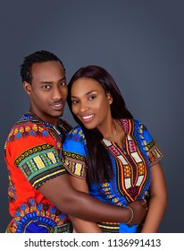 Attractive young African American couple wearing dashiki costume and cuddling each other