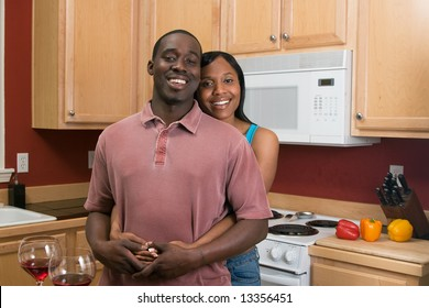 Attractive young african american couple standing in their kitchen with broad smiles on their faces. She is standing behind him and hugging him. Horizontally framed shot.