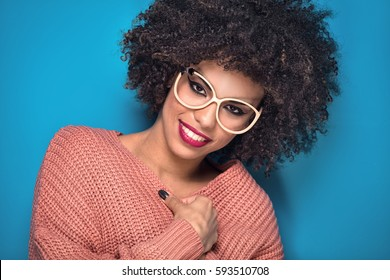 Attractive young African American girl with afro hairstyle and glamour makeup posing in fashionable sweater on blue background.