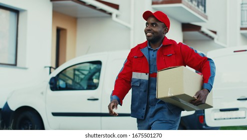 Attractive young African American mailman in red costume and cap taking out percel from a van and walking to the house to deliver it. Outdoors.