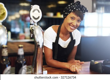 Attractive young African American small business owner dressed in a head scarf and apron leaning on the counter of her pub smiling happily at the camera with a confident smile