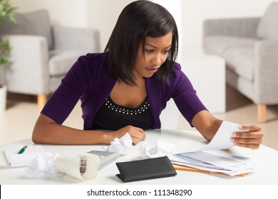 Attractive young African American woman working on finances at home wearing purple jacket sitting at dining table.