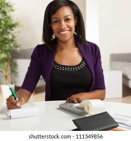 Attractive young African American woman working on finances at home wearing purlple jacket sitting at dining table.