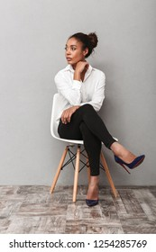 Attractive young african business woman wearing shirt sitting in a chair isolated over gray background, looking away at copy space