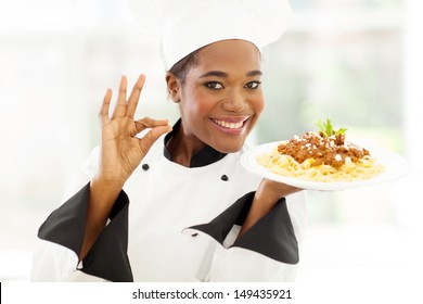 attractive young african chef with delicious pasta dish