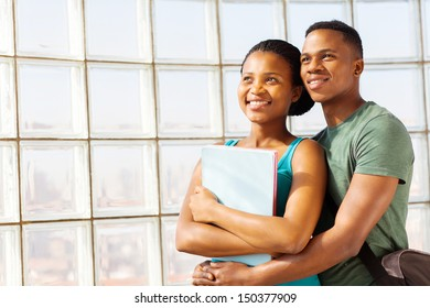attractive young african college couple embracing