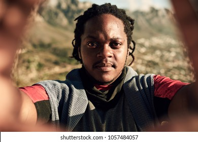Attractive young african guy taking a selfie while on an extreme hike, scaling the side of a rather large mountain as the sun sets on a summer evening.