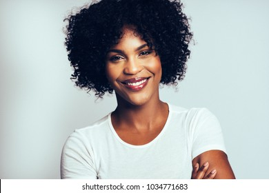 Attractive young African women with curly hair smiling confidently while standing with her arms crossed against a gray background