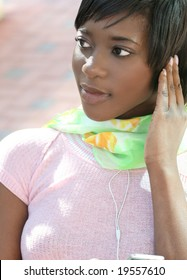 Attractive young African-American female with an mp-3 player, listening to music outdoors