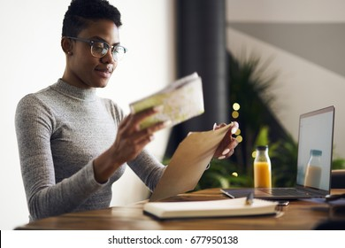 Attractive young afro american businesswoman receiving from post envelope with documentation for project earning money online, professional designer in eyewear packing working papers for mailing