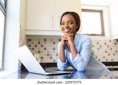 attractive young afro american woman using laptop in kitchen
