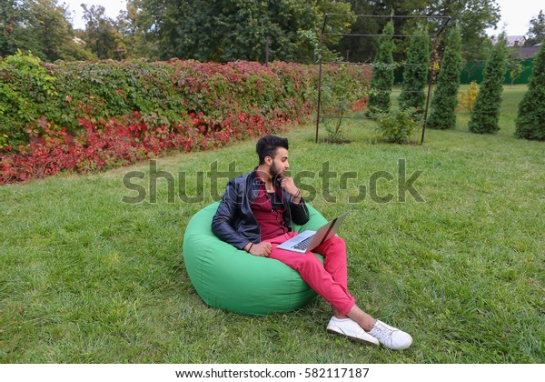 Attractive Young Arabic Guy, Businessman, Student Sits With Laptop in Soft Green Chair, Looks at Computer Screen and in Aside, Speculates About Work, Thinking About Solving Problems, Scratches Beard