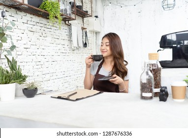Attractive young Asian beautiful caucasian barista in apron smelling aroma of coffee in cup during work in cafe. Startup Small Business Owner Concept. SME Business Concept.