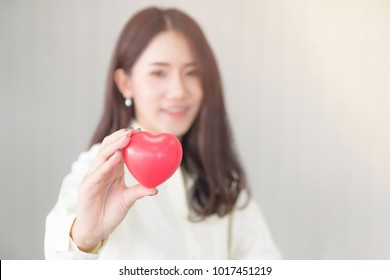 Attractive young asian beautiful woman smiling, happy face and holding red love hearts shape concept for valentine's day and health care. (Selective focus on heart shape and blurred background)
