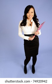 Attractive young Asian business woman in white blouse and black skirt holding a pink clipboard with pen - smiling
