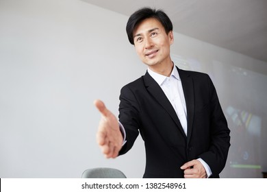 Attractive young asian businessman offering handshake after business deal