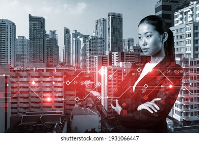 Attractive young Asian businesswoman pondering on technology at business process to achieve tremendous growth in commerce. Tech hologram icons over Bangkok background