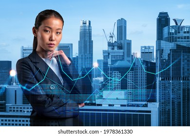 Attractive young Asian businesswoman in suit pondering about new approaches to consultancy to find priorities for venture capital start up to estimate prospective growth. Financial chart on Singapore.