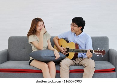 Attractive young Asian couple playing acoustic guitar together in living room. Love and romance people concept.