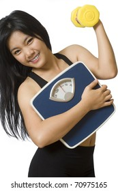Attractive young Asian girl with weight scale and dumbbell