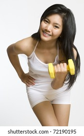Attractive young Asian girl working out with weights