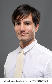 Attractive young Asian guy in white suit, closeup portrait on studio gray background.