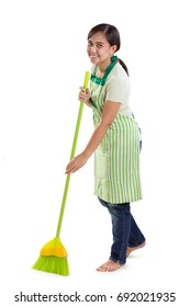 Attractive young Asian housemaid sweeping the floor and smiling to camera. Full length portrait isolated over white