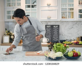 Attractive young asian man looking recipe on digital tablet and cooking healthy food  in kitchen at home.