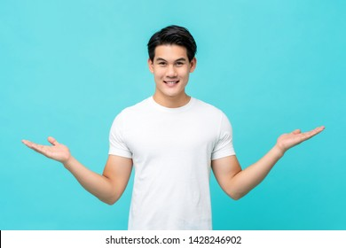 Attractive young Asian man smiling and welcoming heartily with arms open isolated on light blue studio background