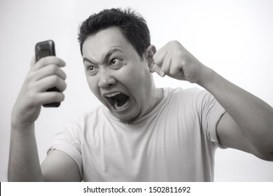Attractive young Asian man talking on his phone, getting bad news, shocked mad angry gesture