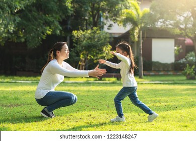 Attractive young asian mother and little cute girl daughter run to hug her mom in garden after back school in evening. Mom and kids feeling relax enjoy playing outside concept. Bonding in asia family.
